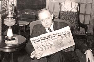 "Gov. Sprague sitting in a chair reading a newspaper with the headline ""Japs Speed Singapore push claim rubber capital taken"""
