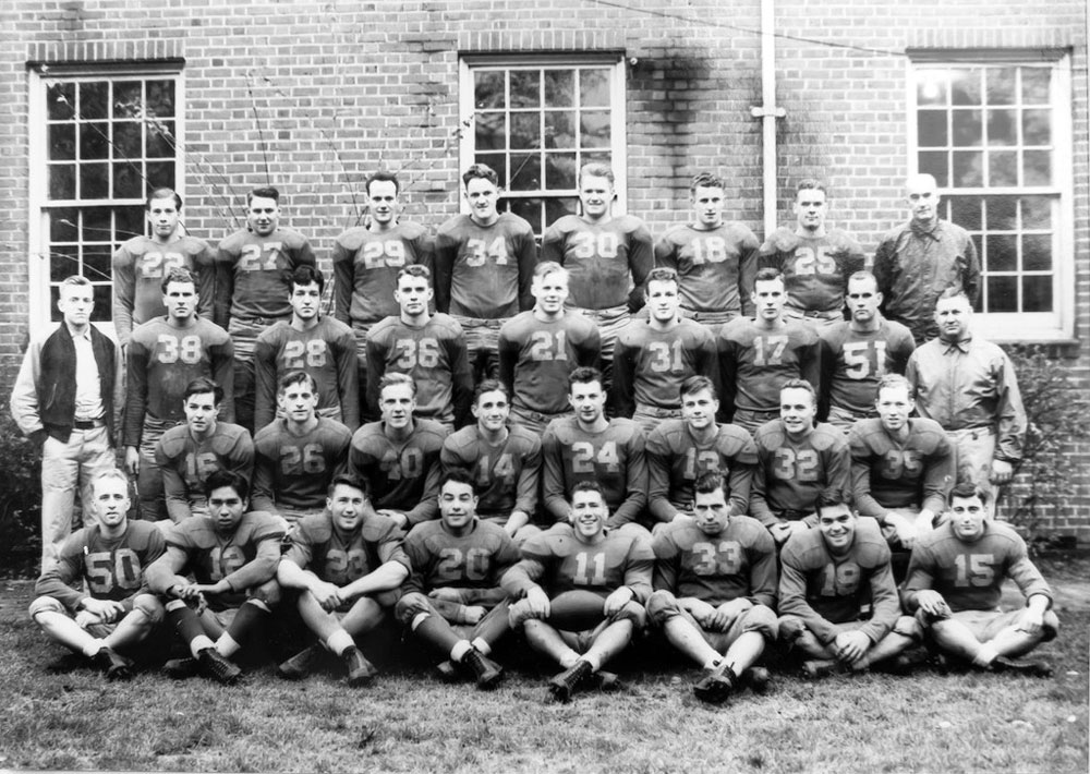 Photo of the football team in front of a brick building.
