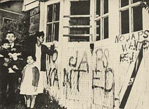 Mother, father, 2 small children stand in front of hate messages spray painted on their home.