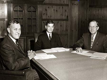 Three men sit at a table with papers in front of them.