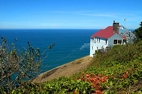 Red roofed cottage on a cliff looks out over blue ocean and clear sky.