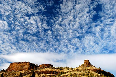 Rock formation shaped like a chimney with blue sky and white clouds in background.