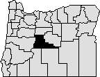 Map of Oregon with a section near the center blacked out to represent Deschutes County.
