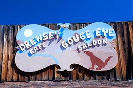 Sign has drawing of dog & sand dunes with name of cafe & saloon above.