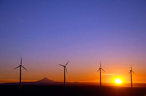 Four wind turbines shown with a colorful sunset in the background.