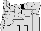 Map of Oregon with a section in the north-center blacked out to indicate Gilliam County.