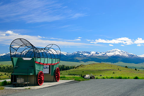 A replica covered wagon stands to the side of a highway with snow capped mountains in the distance.