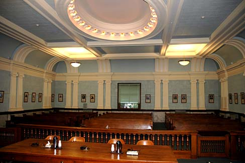 Wooden audience benches in 3 rows as seen from judge's bench in Clatsop County Courthouse.