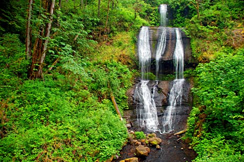 a waterfall falls over 3 rock terrace formations. Lush green foliage grows on the banks at the sides.