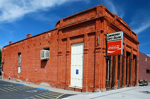 Brick building on corner of block with Coca-cola sign out front.