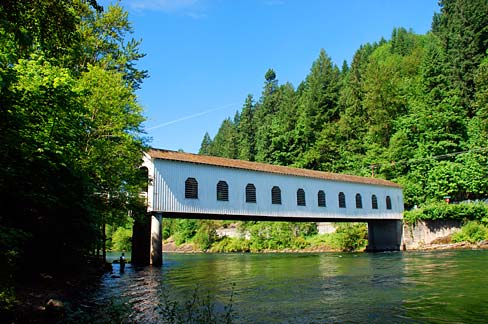 Covered bridge spans a river in early spring or summer. Thick green trees of both deciduous and evergreen variety on banks.