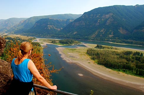 Woman stands at view point with hands on railing looking out over Columbia River.
