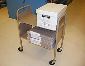 Metal cart with wheels holding archive boxes.