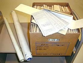 A box on a table with folded files inside and large rolled up, long papers to the side (probably maps).