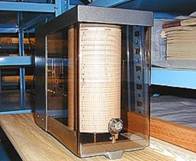 A chart on a circular tumbler encased in glass and set on a wooden table. A temperature gauge is attached to the front.