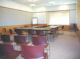 A conference room with a window, flip chart on stand, tables and chairs.