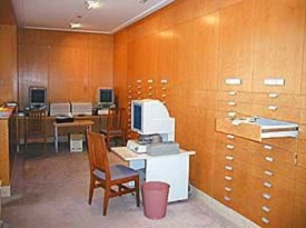 East alcove walled with wooden drawers and housing 2 desks, 3 chairs and 3 computer terminals for accessing microforms.