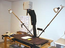 Camera mounted about 4 feet above a table with lights on movable arms to the side.