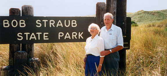 "Bob Straub & his wife stand before a sign reading ""Bob Straub State Park."""