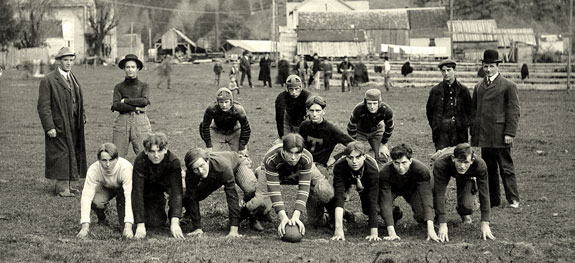 Young men on a football team pose with a football and their coaches.
