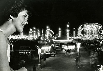A woman looks at the bright lights of the State Fair at night