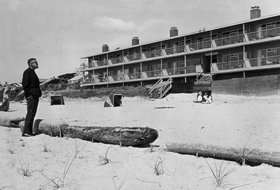 Tom McCall stands on the beach next to a log and looks at a motel. 2 floors are visible with 8 rooms each.