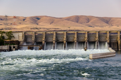 A hydropower dam in The Dalles consists of a concrete structure with a navigation lock, spillway, gated powerhouse & fish passage facilities
