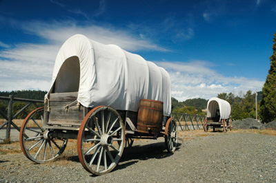 2 covered wagons stnd in a line on a dirt trail.