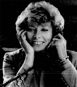 Norma Paulus holds a telephone receiver to one ear. She is smiling.