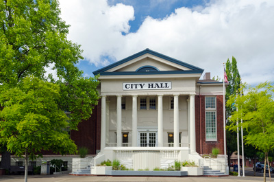 3 story historic City Hall building in colonial style with 6 pillars holding up the overhang above front door. Brick walls.