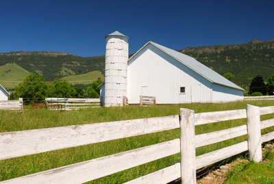 A barn with a grain silo attached at one end and a picket fencing running along the side. Low mountains are seen in the back.