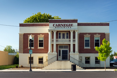 The Carnegie Building, built in 1911, of brick and stone with a stairway leading to the 2nd floor and a deck above the door.