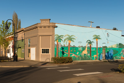 A mural on the side of a building shows palm trees, a giraffe, an elephant and other animals on a green landscape.