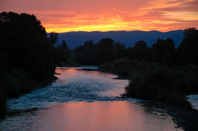 Below, a swiftly running river. On the horizon a sunset in vibrant colors. Trees line the landscape.