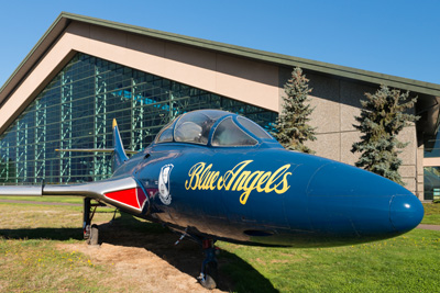 "A jet known as a Grumman F9F-8, airplane flown by the Blue Angels. ""Blue Angels"" is written in script on the side nose of plane."