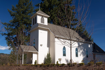 Small church with bell town in front topped with cross. Stained glass windows line the side. Front porch is covered.