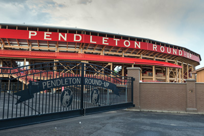 Wide gates to the Pendleton Round-Up arena. The stands where people sit are seen behind the gates under a long roof.