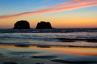 Sunset along the beach throws pink & orange colors into the sky & reflects on wet sand. Twin rock formations in the ocean near.