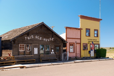 "Single story log building with ""This Ole House"" printed on top. 2 buildings with false fronts like old time western towns."