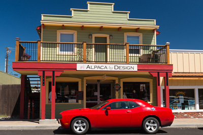 2-story building with porch on 2nd level. A red sports car is parked in front. Sign on building says Alpaca by Design.