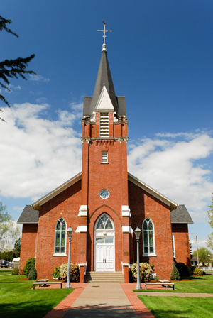 Brick church built in the Gothic Revival Style. Includes lofty spire, pointed arch openings, steeply pitched gable roof. Spire is surmounted by a Latin cross. Main entry is flanked by buttresses with sandstone coping. Rose Window fitted with stained glass is above the arched entry.