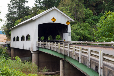 Covered bridge with side windows with curved tops. 4 windows on each side, portals with flat arched openings & exposed false beams at the gable ends