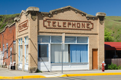 "Single story cream colored brick building on street corner. The word ""Telephone"" in red brick on 2 sides above windows."