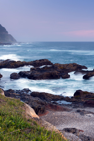 A rocky coast line at dusk with white capped waves.