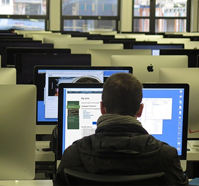Student sitting at computer with MyVote on screen.