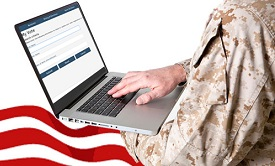 Person in military outfit using laptop.